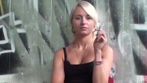 Blondýnka v černých šatičkách kouří